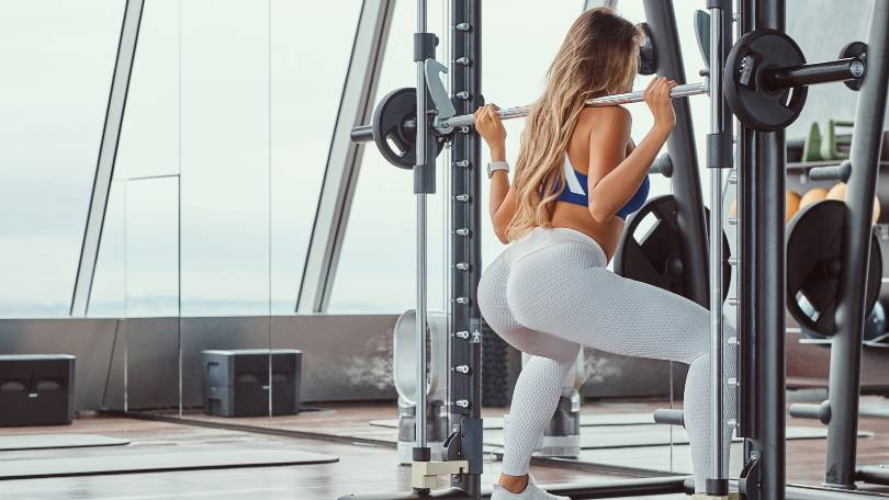 Fitness Girl Doing Squats on Smith Machine