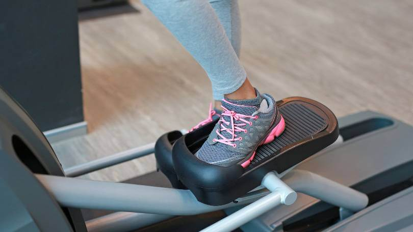 Close up Foot of fitness girl running on Elliptical machine
