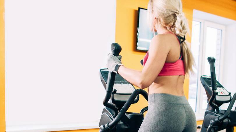 Fitness young girl on elliptical machine