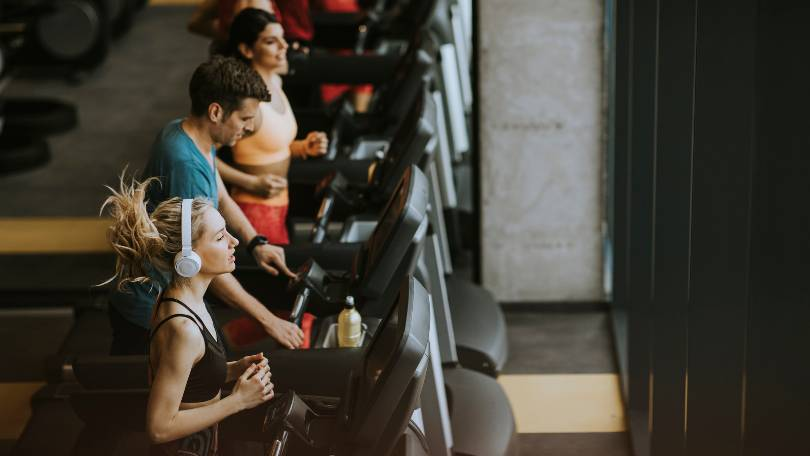 Young People Running on Treadmills in Modern Gym