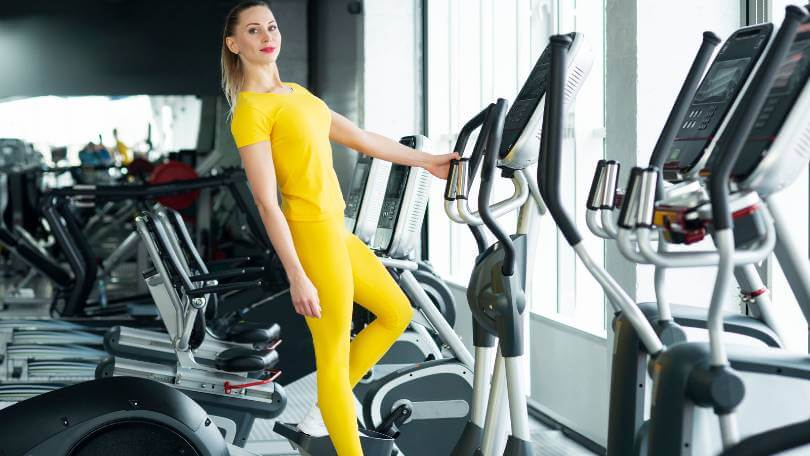 Young woman standing on Elliptical Machine in gym