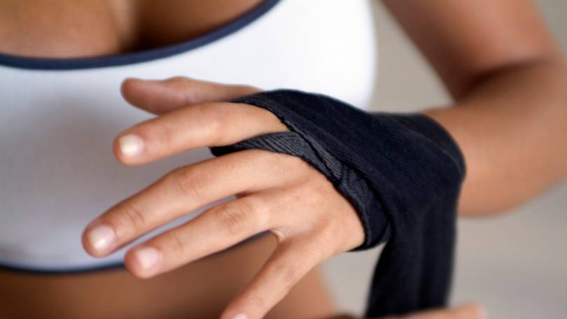 woman wrapping black wrist wrap